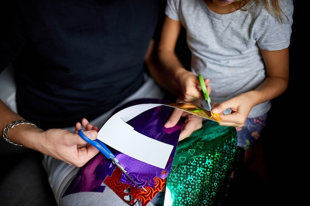 Figlia e padre si divertono a fare artigianato insieme a casa sul divano, tagliando una carta con le forbici, luce scura,
