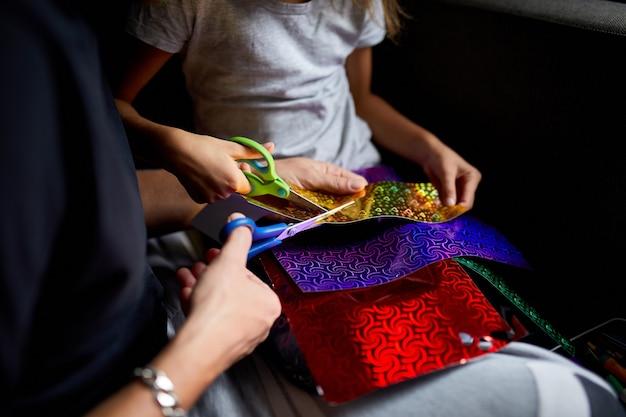 Figlia e padre si divertono a fare artigianato insieme a casa sul divano