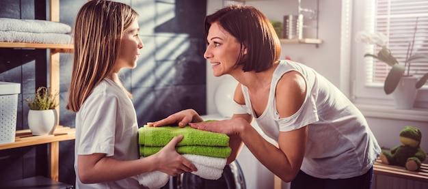 Figlia che dà gli asciugamani piegati verdi della madre Foto Premium