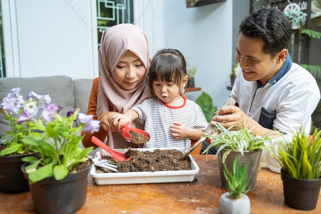 La figlia è assistita da sua madre tenendo una piccola pala per prendere terra e suo padre tiene una piccola pala