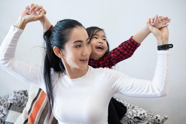 La figlia abbraccia e gioca con sua madre e ride e sorride felice sul divano mentre si rilassa a casa.