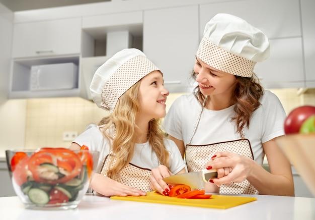Figlia e mamma in cappelli da cuoco che cucinano insalata di verdure.