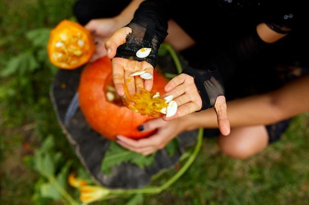 Figlia e madre mani tira semi e zucca materiale fibroso prima di intagliare per halloween, prepara jack o'lantern. decorazione per la festa, piccolo aiutante familiare, vista dall'alto, da vicino, copia spazio