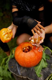 Figlia e madre mani che tira semi e materiale fibroso da una zucca prima di intagliarla per halloween, prepara jack o'lantern. decorazione per la festa, piccolo aiutante di famiglia,