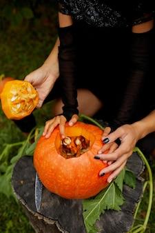 Figlia e madre mani che tira semi e materiale fibroso da una zucca prima di intagliarla per halloween, prepara jack o'lantern.
