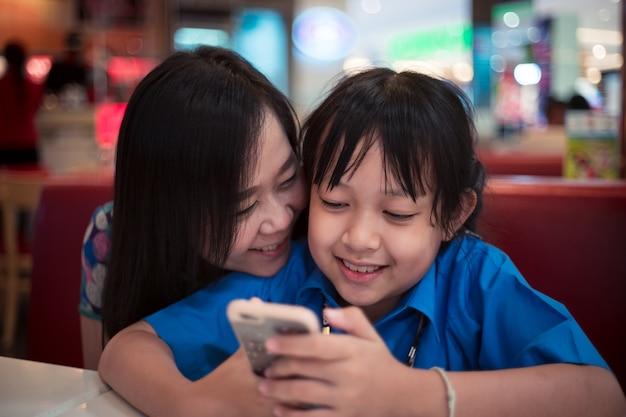 Figlia e madre alla ricerca di uno smartphone con sorriso e felice