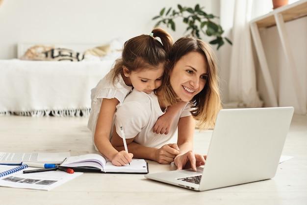 La figlia gioca con mamma e gatto mentre la mamma lavora al computer