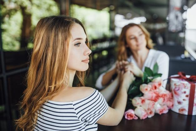 La figlia presenta un regalo e un mazzo di rose in un caffè con terrazza estiva in abiti casual.