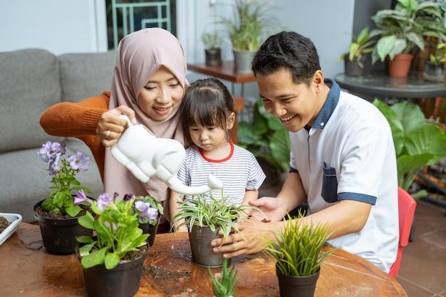 La figlia vede sua madre che tiene un annaffiatoio mentre innaffia le piante e suo padre che tiene una pianta in vaso