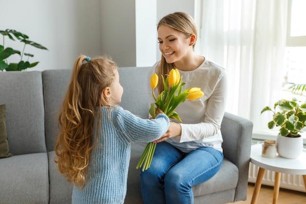 Figlia con bouquet di fiori, cartolina si congratula con la mamma