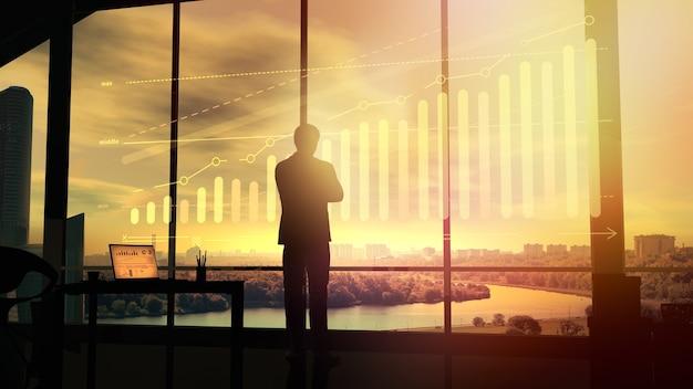 All'alba, un uomo d'affari guarda un ologramma di un grafico di crescita
