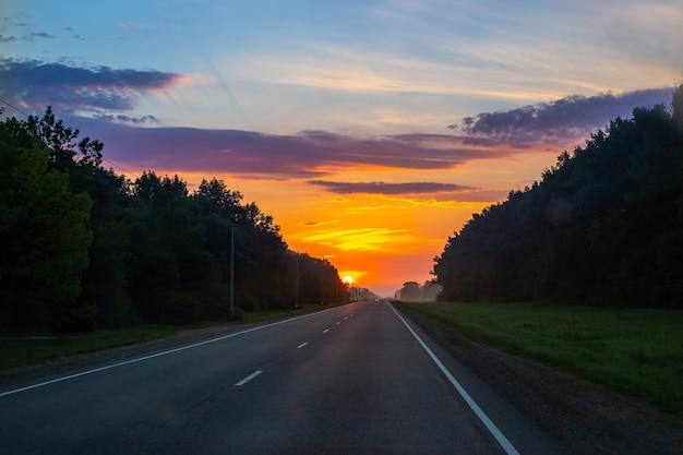 Alba sulla strada. il sole splende sullo sfondo del cielo con le nuvole, intorno alla foresta. paesaggio mattutino.