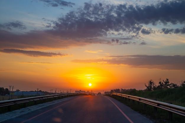 Alba sulla strada. il sole splendente sorge contro il cielo arancione. paesaggio mattutino.
