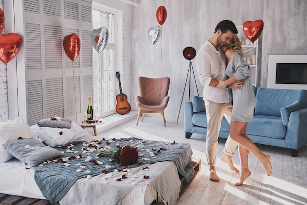 Giornata per celebrare il loro amore. per tutta la lunghezza di una bella giovane coppia che si abbraccia e sorride mentre si trova nella camera da letto piena di palloncini