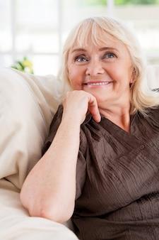 Sognare ad occhi aperti. donna anziana premurosa che tiene la mano sul mento e sorride mentre è seduta su una sedia