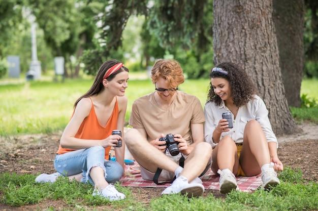 Giorno libero, picnic. tre giovani amici gioiosi con drink che guardano foto sulla fotocamera seduti su una coperta all'aperto in una giornata calda