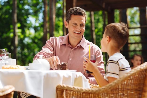 Giornata con il padre. piccolo ragazzo dai capelli biondi che si sente molto felice e soddisfatto mentre trascorre una giornata fantastica con il padre