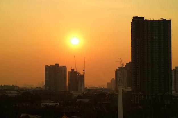 Abbagliante sole della sera sul cielo dorato sopra la sagoma del cantiere della città