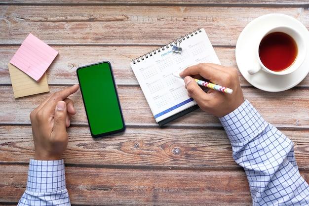 Concetto di scadenza con data di marcatura a mano sul calendario e utilizzo di smart phone