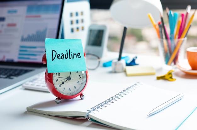 Scadenza e concetti di lavoro con testo sulla sveglia sulla scrivaniamotivazione e gestione