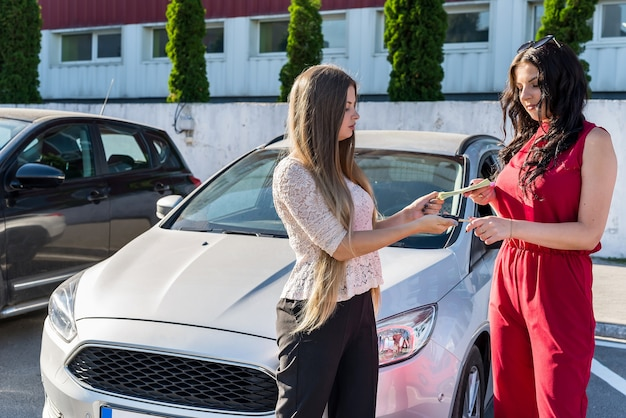 Concessionario e cliente che scambiano banconote in dollari e chiavi della macchina