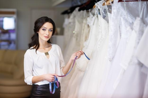 Consulente del rivenditore sullo sfondo di abiti da sposa