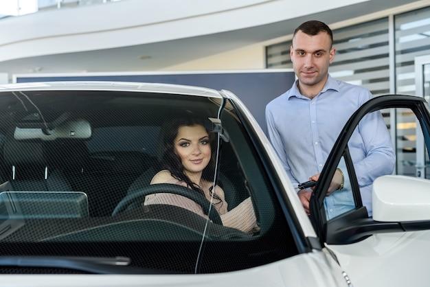 Commerciante che dà le chiavi dalla macchina nuova alla bella donna