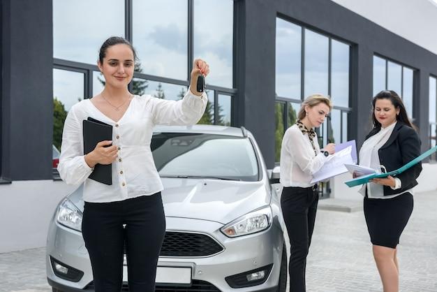 Concessionario che tiene le chiavi dalla nuova automobile. tre signore con cartelle in posa all'esterno dello showroom