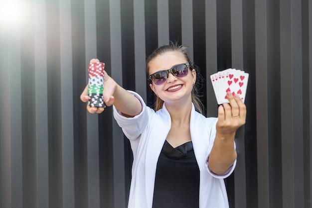 Commerciante con fiches da poker e carte da gioco su sfondo astratto. donna in occhiali da sole che tengono i chip del casinò in posa per la fotocamera
