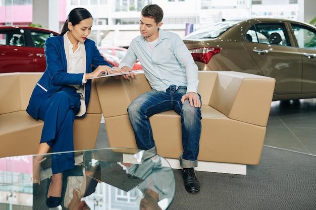 Responsabile della concessionaria che annota i dettagli del cliente e il preferencer prima di offrirgli un giro di prova dell'auto