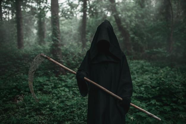 La morte in una felpa con cappuccio nera con una falce nella foresta