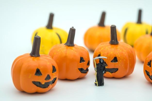 Figura in miniatura del diavolo della morte che sta con la presa del fronte della zucca di halloween isolata