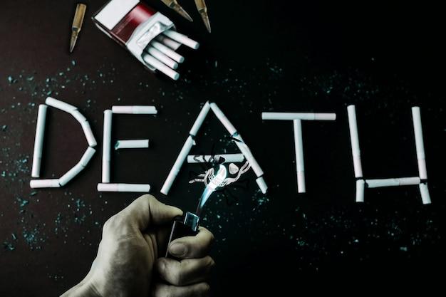Segno di morte dalle sigarette. cranio dal fumo. abitudine pericolosa. nocivo per la salute. l'uomo tiene l'accendino nelle mani.