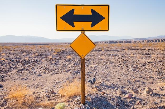 Valle della morte, california. segnale di direzione nel mezzo del deserto.