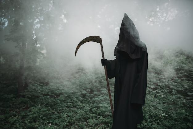 Morte con una falce nell'oscura foresta nebbiosa