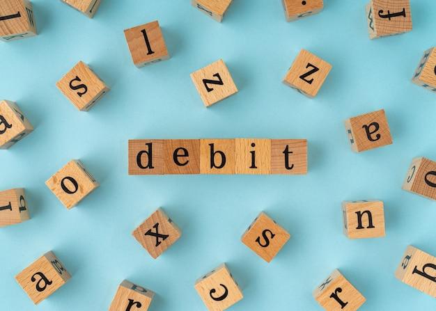 Parola di debito sul blocco di legno. vista piatta su sfondo blu.