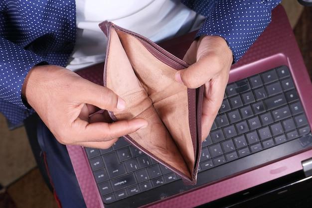 Il concetto di debito con la mano dell'uomo apre un portafoglio vuoto con lo spazio della copia.