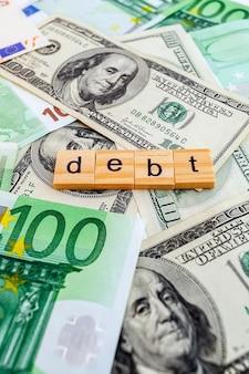 Iscrizione di debito su cubi di legno sulla trama di dollari americani e banconote in euro