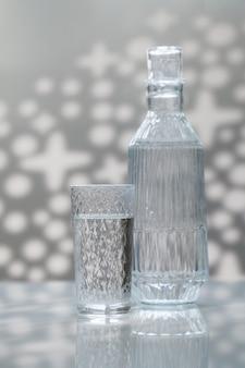 Un decanter e un bicchiere di acqua potabile.