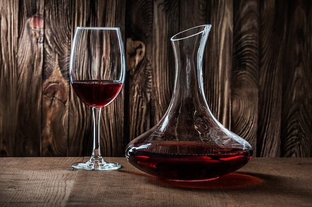 Decanter e vetro con vino rosso su legno vintage