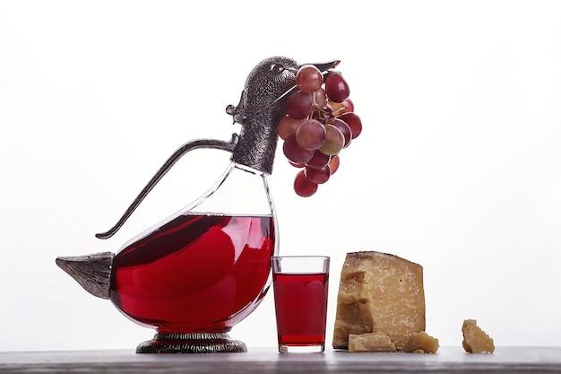 Un decanter di vino rosso, un bicchiere di vino, formaggi costosi, formaggio con muffa, formaggio nero e uva. su sfondo bianco. posto per il logo.