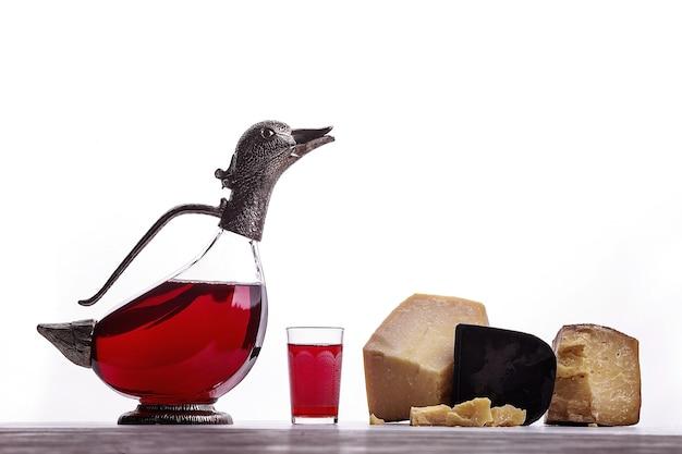Un decanter di vino rosso, un bicchiere di vino, formaggi costosi, formaggio con muffa, formaggio nero. su sfondo bianco. posto per il logo.