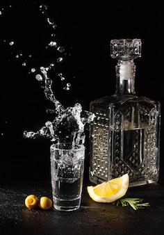 Un decanter e un bicchierino di vodka o altra bevanda alcolica incolore su sfondo nero