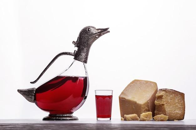Decanter con vino a forma di anatre, bicchiere con vino, prosciutto di parma e costoso formaggio blu. su sfondo bianco.