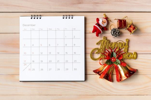 Calendario di dicembre e decorazioni natalizie - babbo natale e regalo sulla tavola di legno. natale e felice anno nuovo concetto