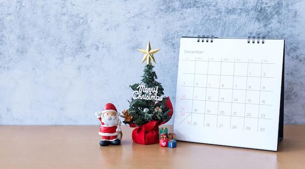Calendario di dicembre e decorazioni natalizie - babbo natale, albero e regalo sulla tavola di legno. natale e felice anno nuovo concetto