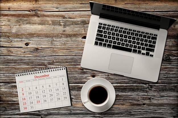 Dicembre nel calendario, tazza di caffè e laptop