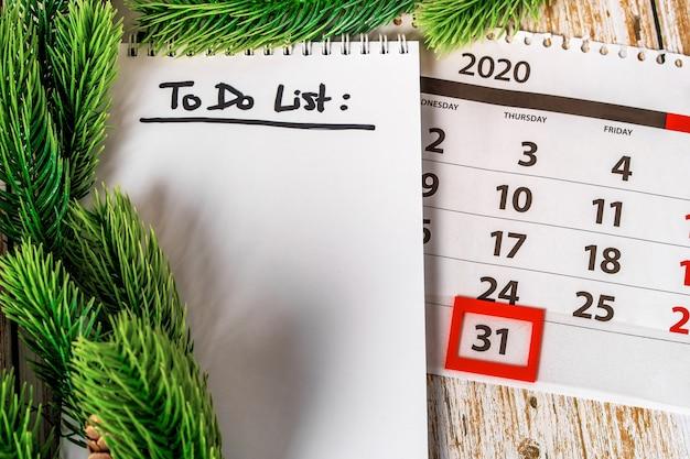 Calendario di dicembre e blocco note con per fare la lista su un tavolo di legno