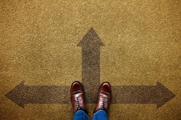 Decisione nella vita o nel concetto di affari. persona indecisa in piedi sulla direzione della freccia in avanti, sinistra e destra. vista dall'alto