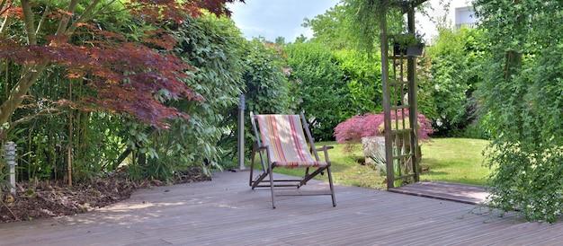 Sedia a sdraio su una terrazza in legno e giardino
